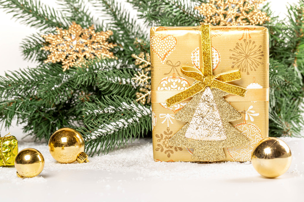 Winter holidays background with golden gift, branches and balls