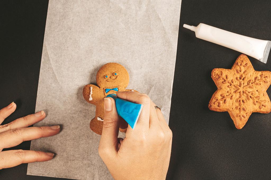 Female hands paint christmas gingerbread cookies