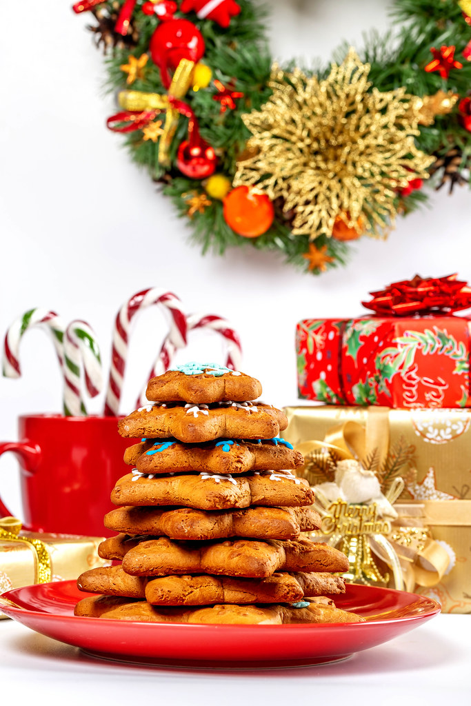 Christmas tree made of gingerbread cookies with gifts, sweets and wreath