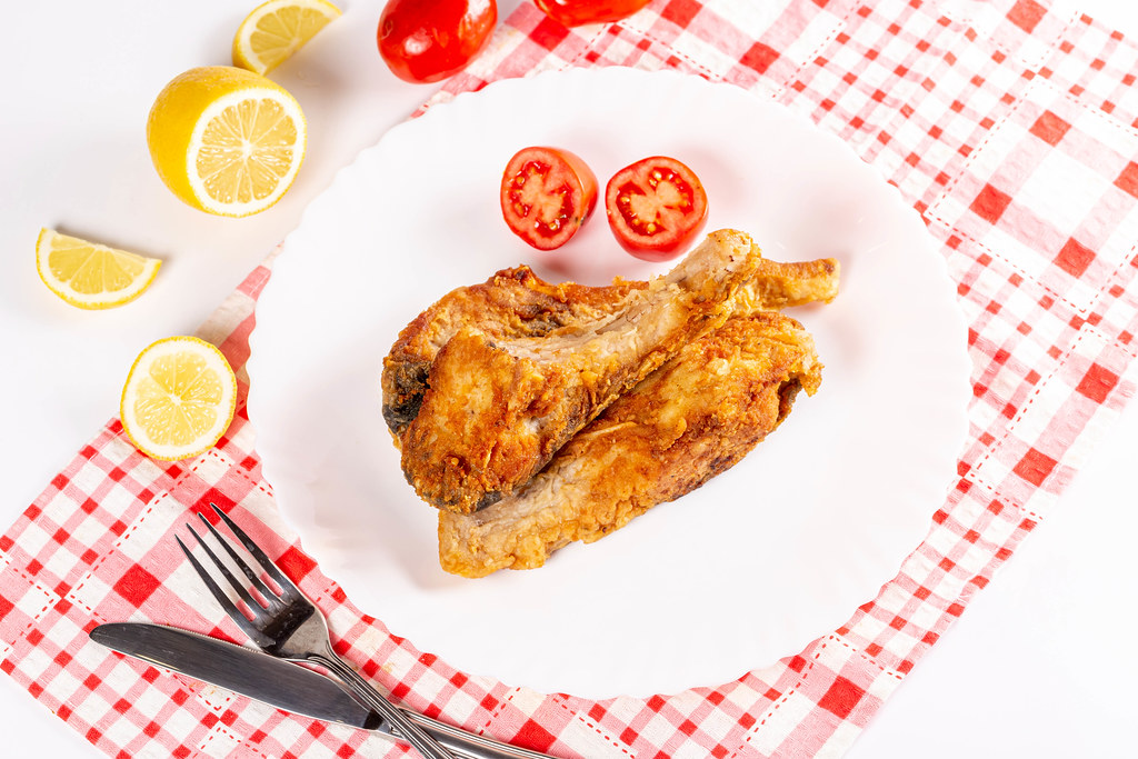 Fried fish carp with tomatoes and lemon