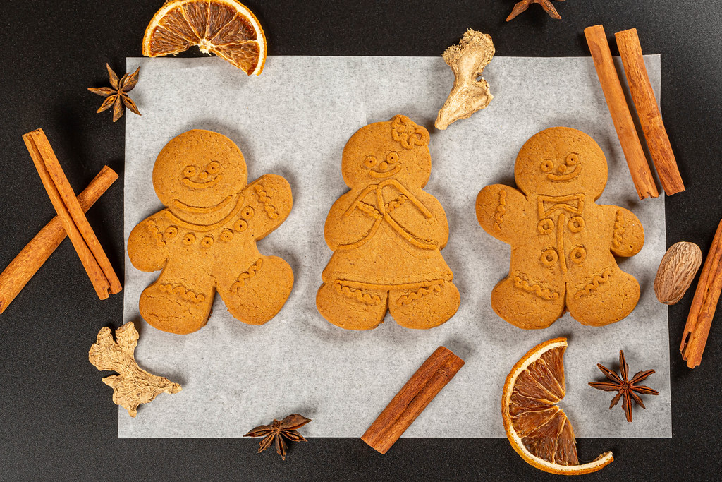 Festive gingerbread men on parchment paper with anise, dried orange, cinnamon and ginger