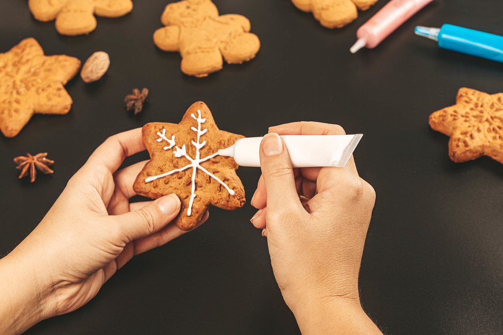 Decorating the gingerbread snowflake with white icing