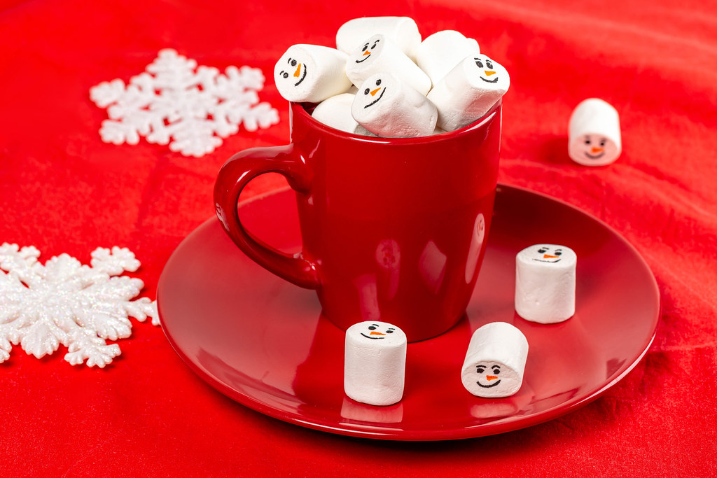 Red mug with marshmallows on a red background