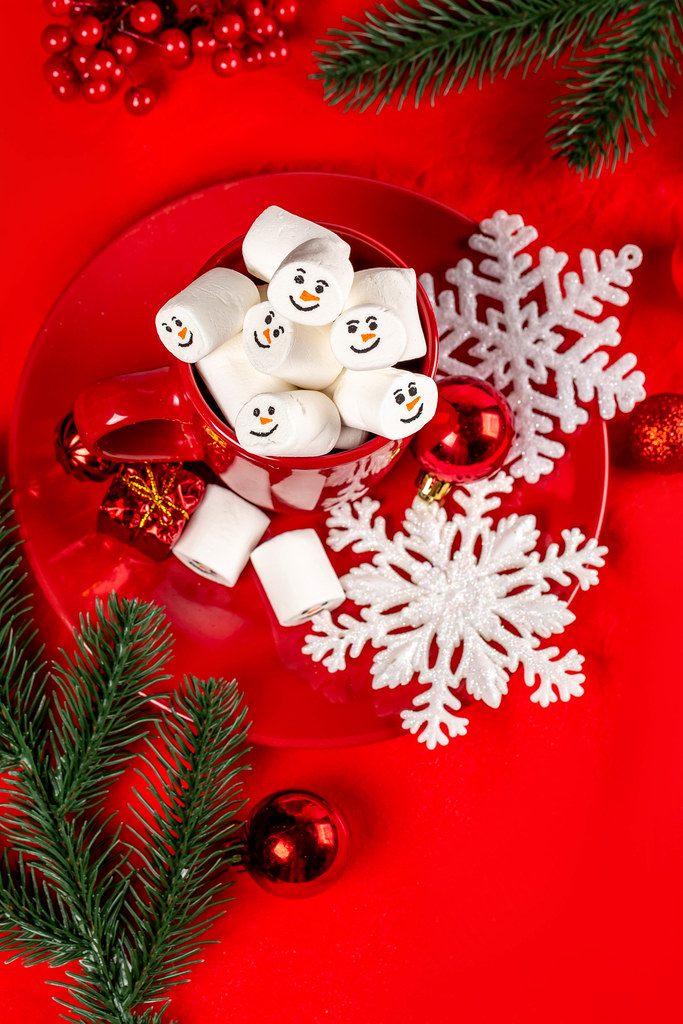 Christmas mood concept, marshmallows in a cup with decor and branches of a christmas tree on a red background