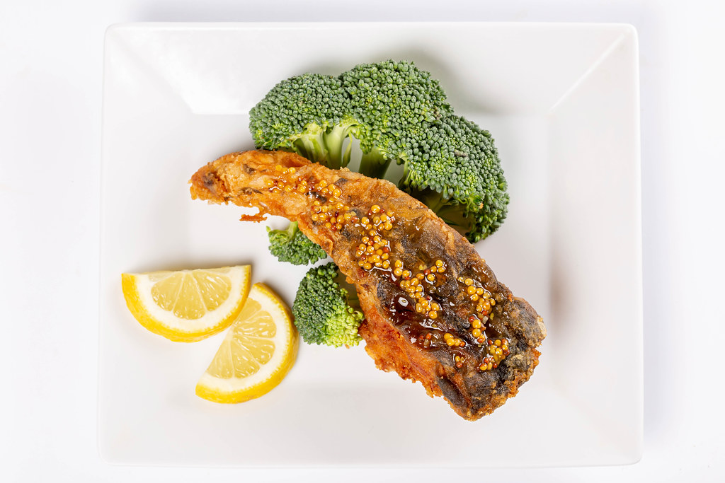 Piece of fried carp fish with broccoli and lemon, top view