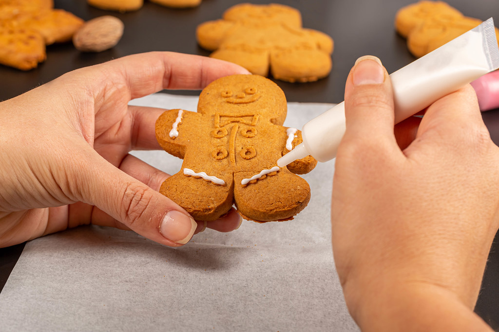Hands decorate christmas gingerbread with glaze