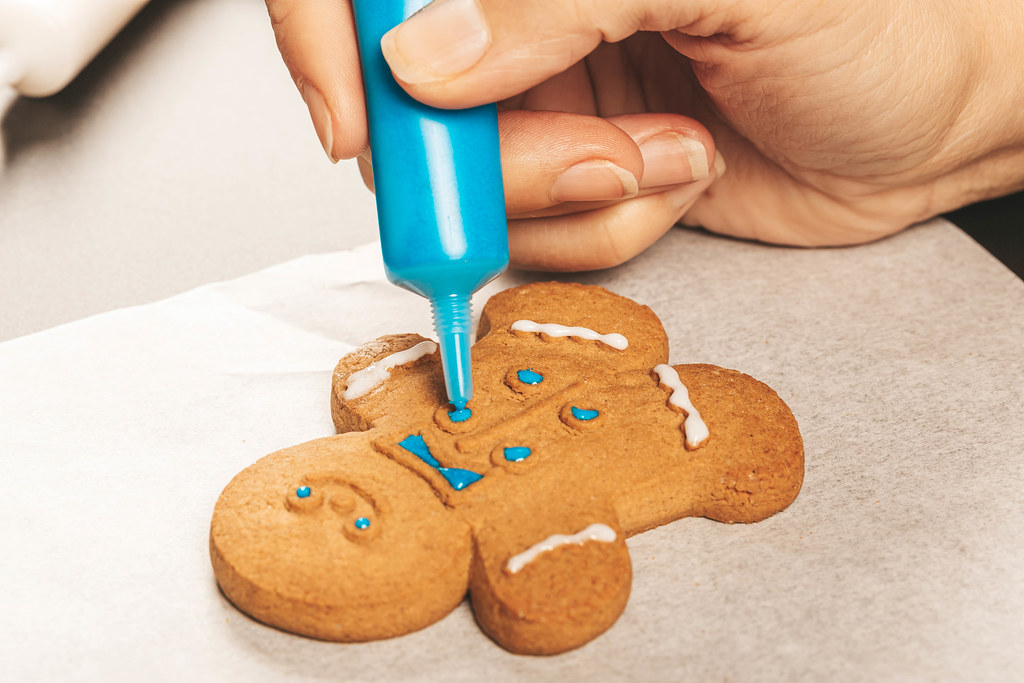 Woman hands decorating homemade gingerbread cookies with icing, close up. Festive culinary and new year traditions concept