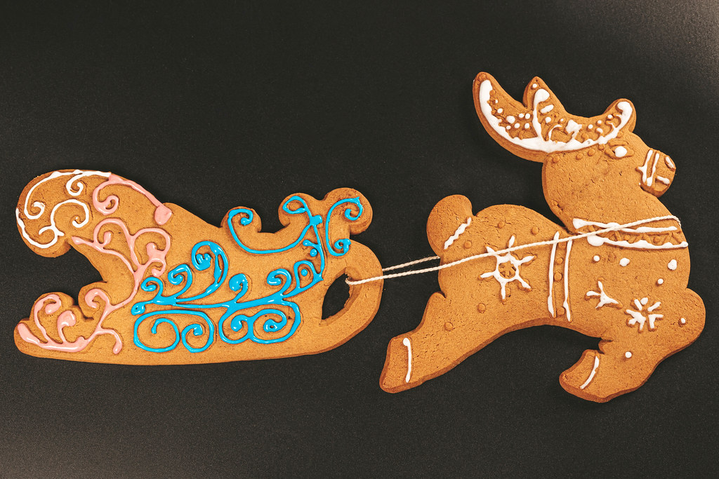 Top view, gingerbread deer and sleigh on black background