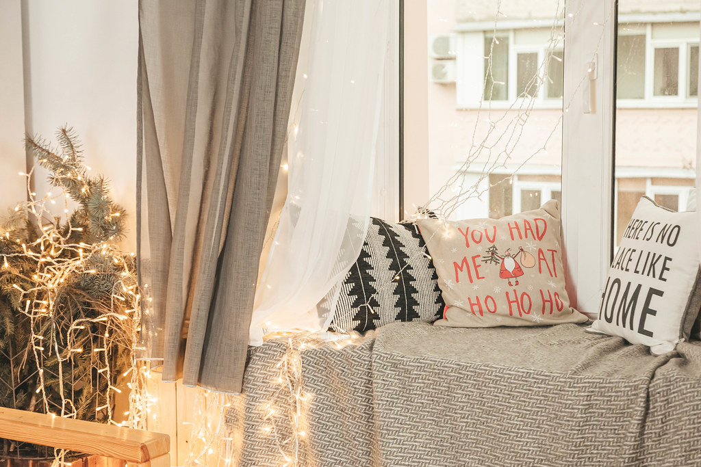 Decorated room for christmas with pillows on the windowsill and glowing garlands