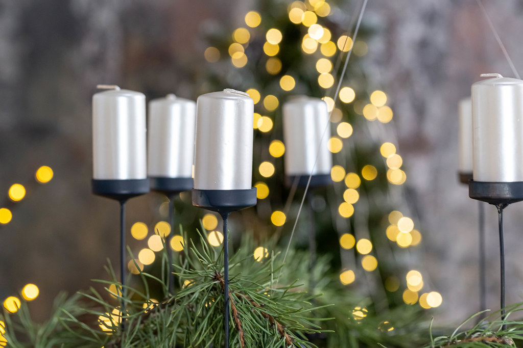 Candles on a blurred background of a christmas tree and glowing garlands