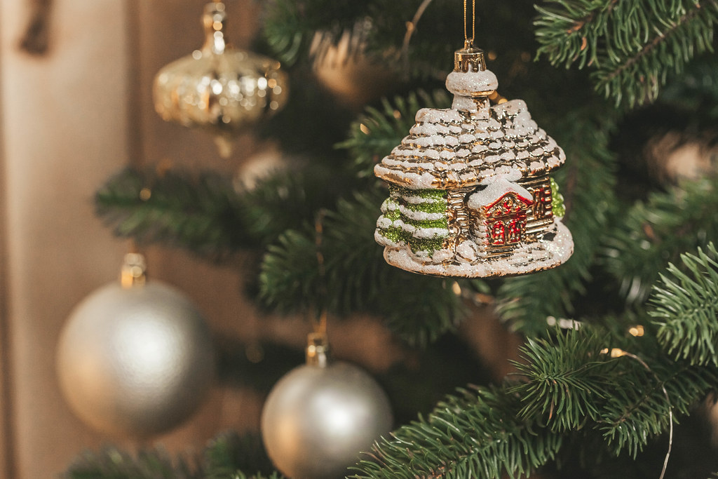 Close-up decoration of a small house hanging on a christmas tree