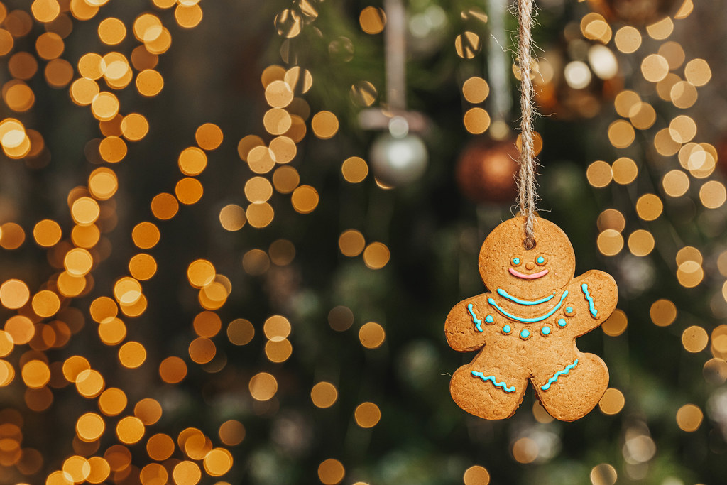 Gingerbread cookie man on golden christmas bokeh background