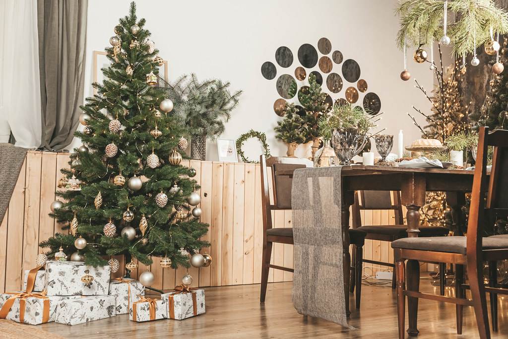 Christmas decorated room interior with table with plates, wine glasses and candles