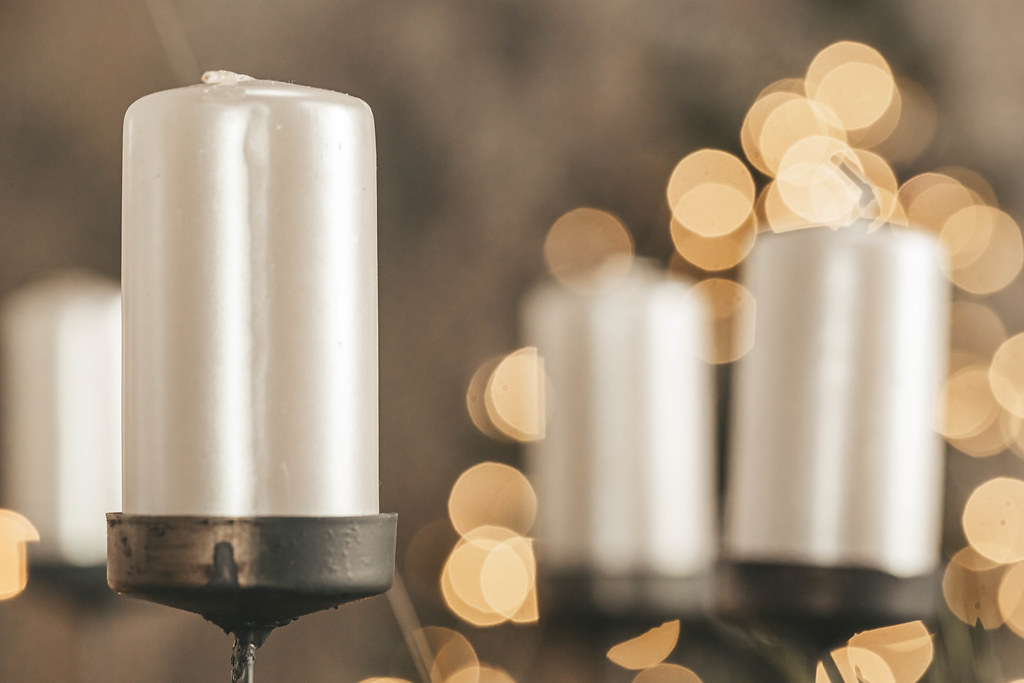 White candles on a golden bokeh background