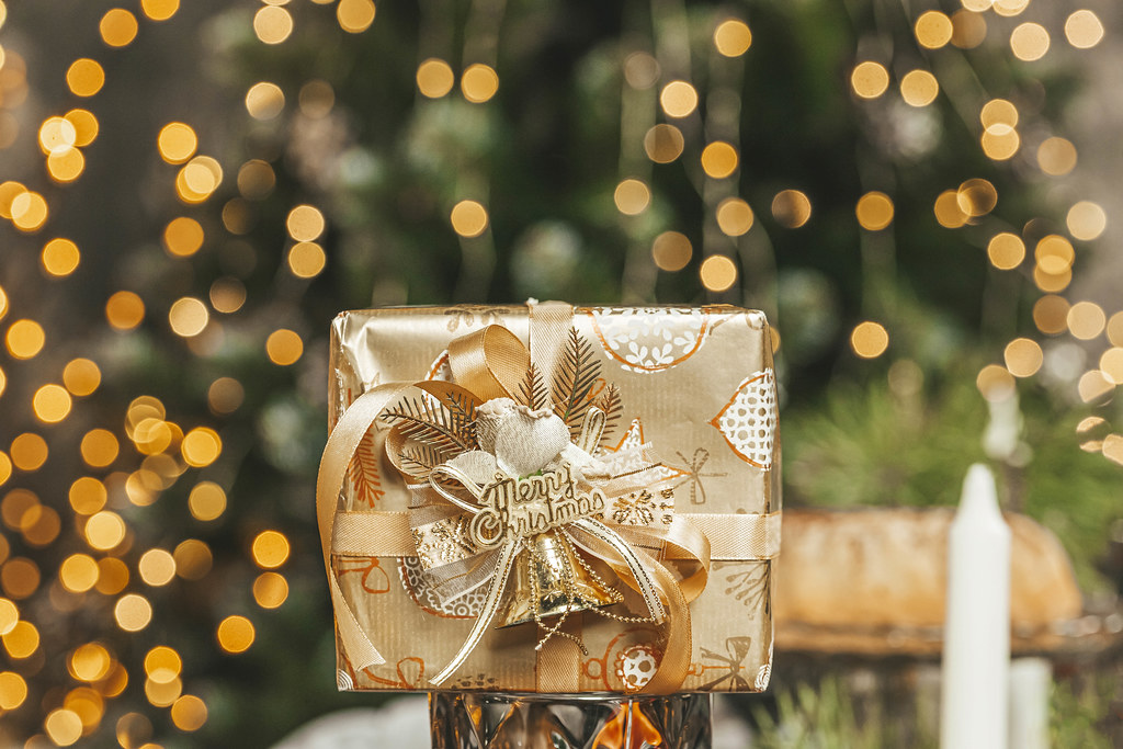 Golden present on a blurry background of a christmas room with garlands