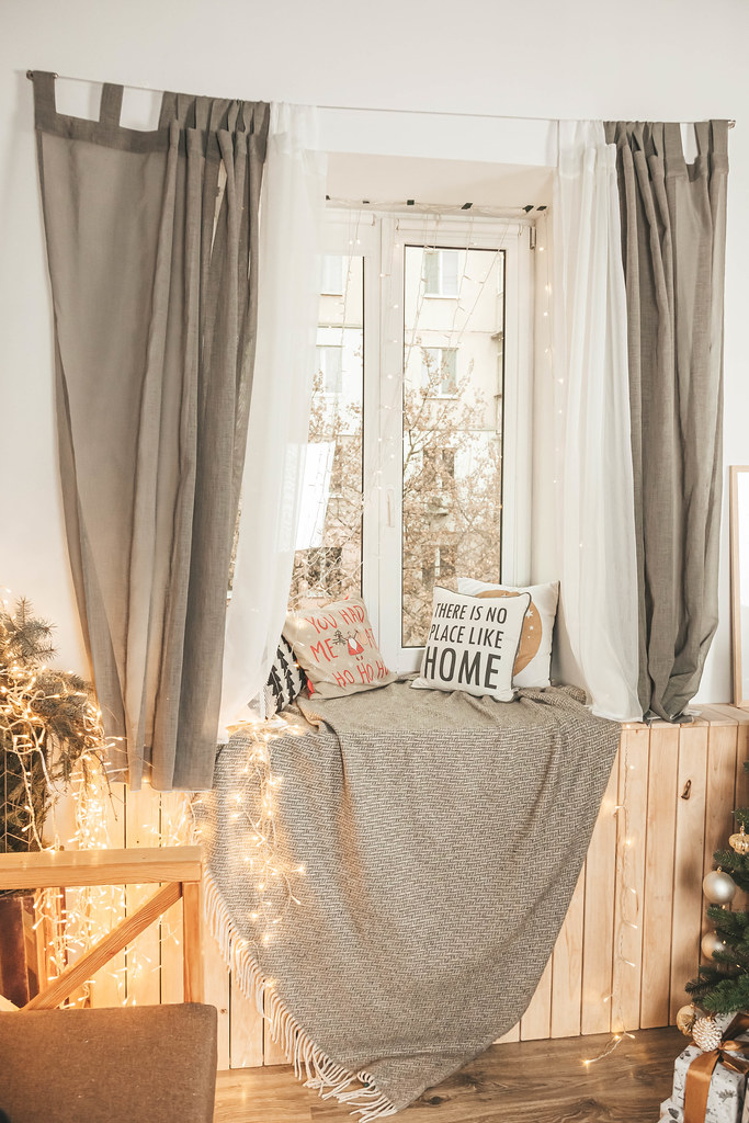 Window with garlands, pillows and a plaid on the windowsill, the concept of home decoration for the winter holidays