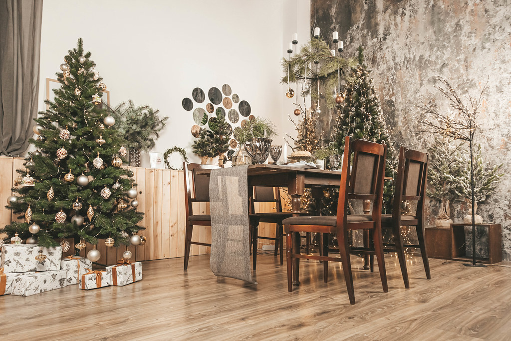 Spacious decorated living room with christmas trees and dining table