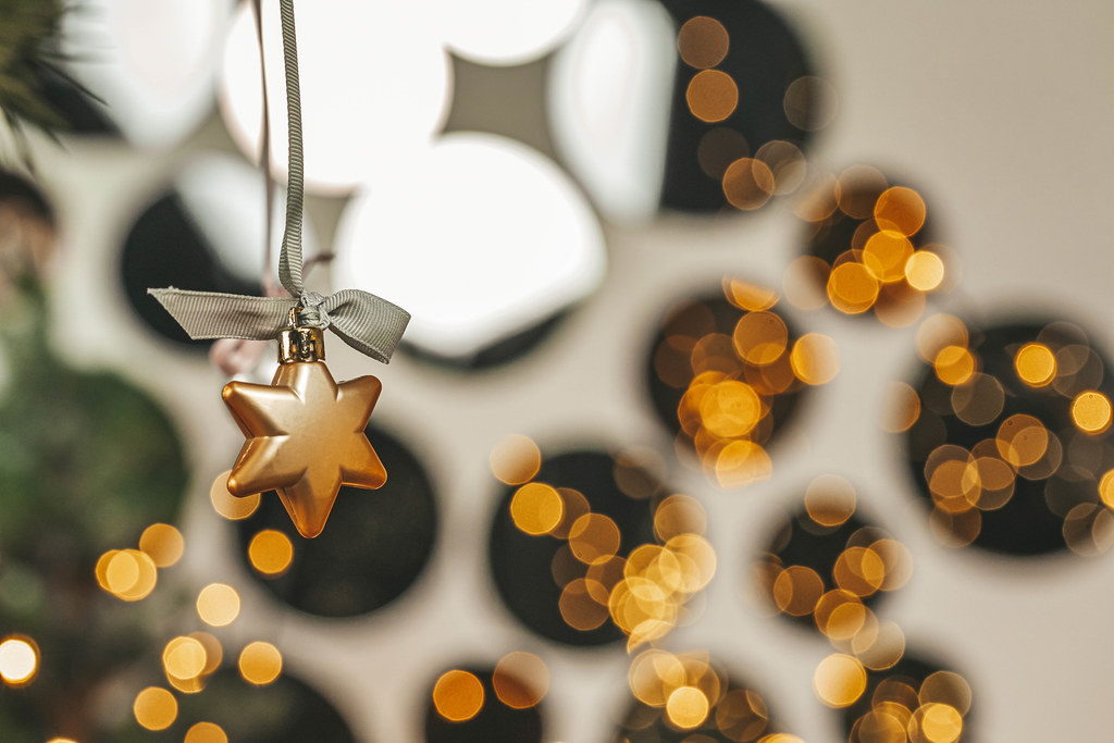 A star decoration hanging on a christmas tree with mirrors and golden bokeh in the background
