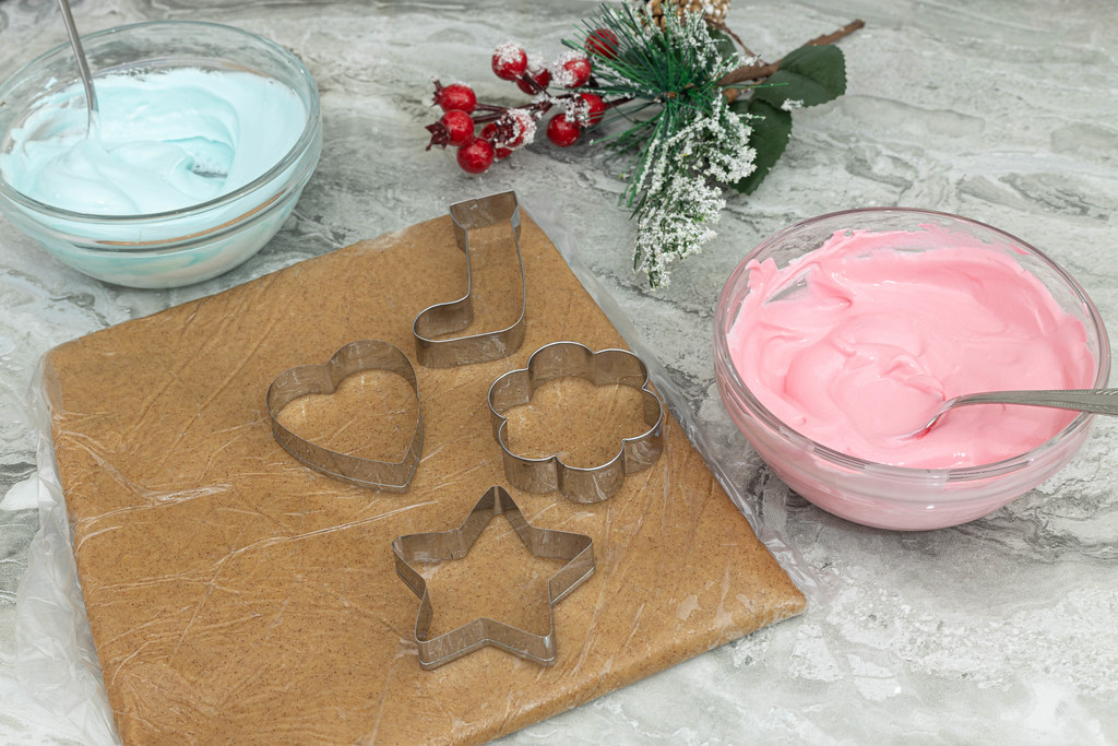 Preparing Christmas cookies with cookie templates and colorful creams