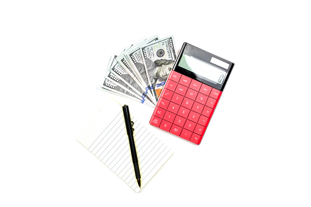 Money, calculator, notepad and pen on white background