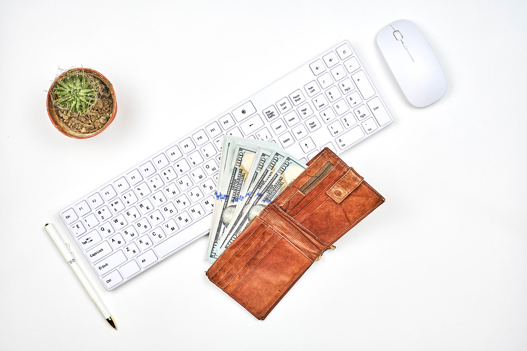 A wallet with US dollars, PC keyboard and mouse at workplace