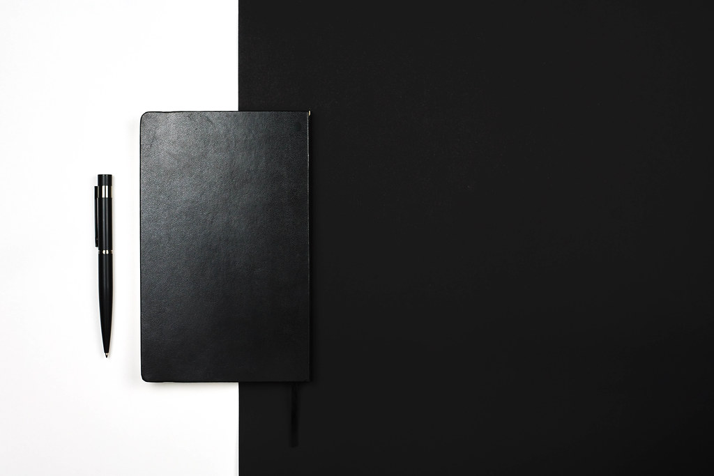 A black leather notepad on black and white background