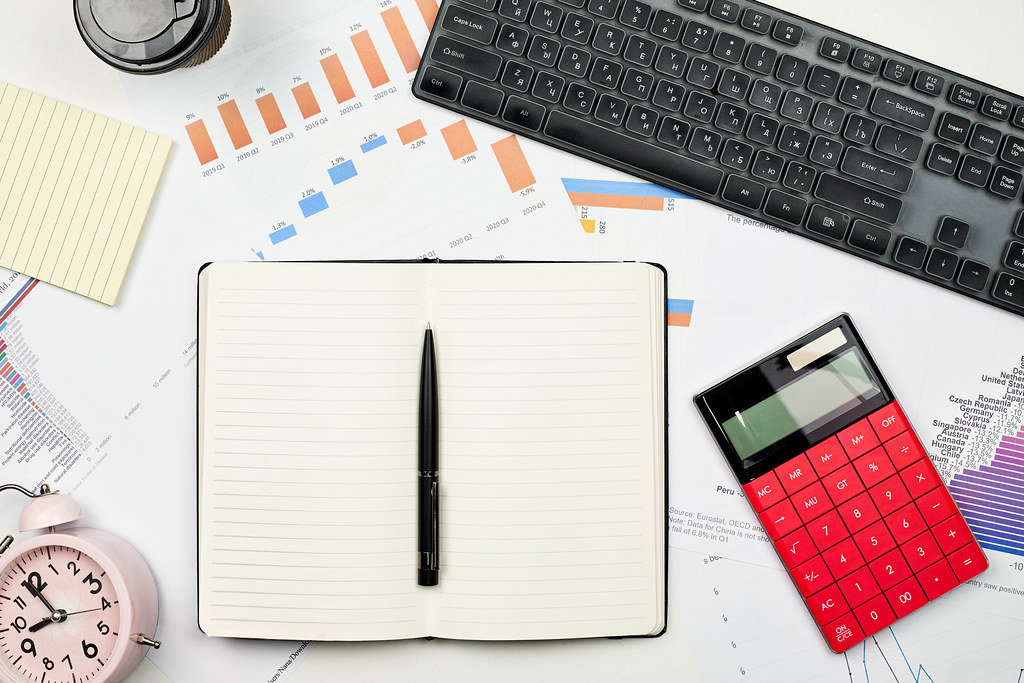 Blank notepad with financial graphs, calculator, alarm clock and keyboard on the workplace