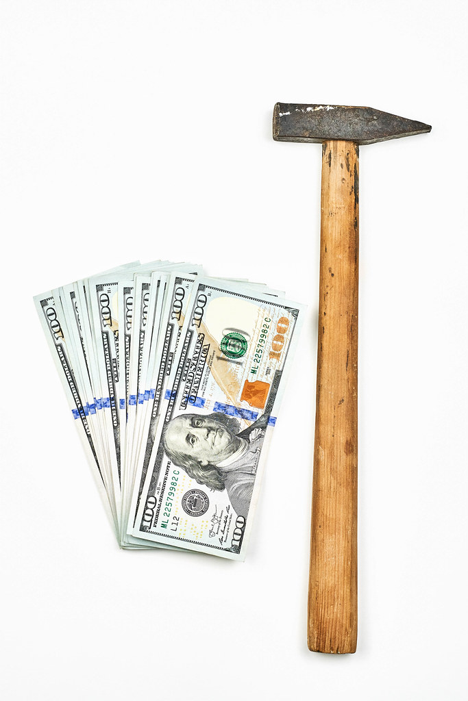 A hammer and money on white