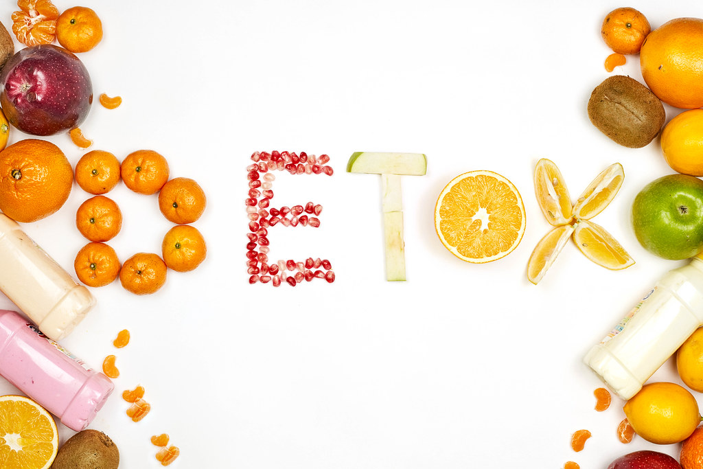 Colorful fruit background with - Detox word made with different raw fruits slices