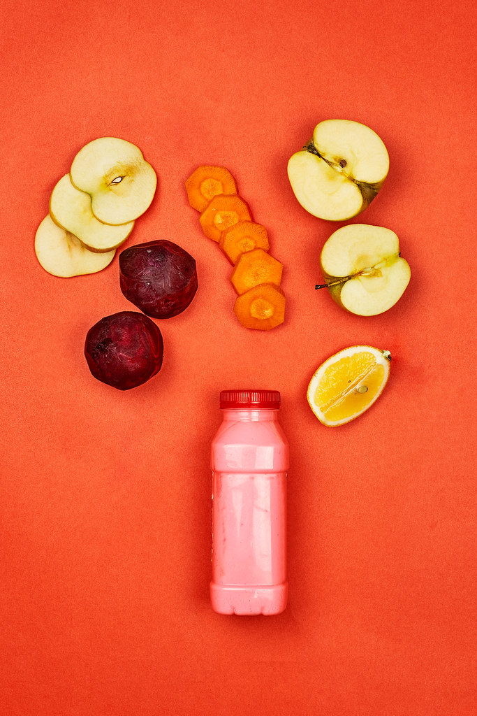 Detox juice with organic fruits and vegetables cuts on red background