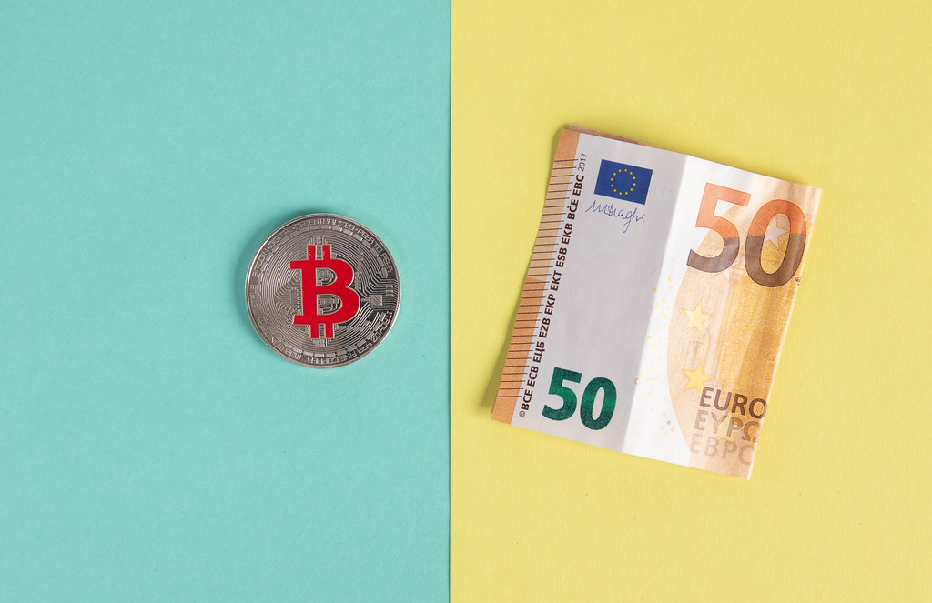 SIlver Bitcoin coin and folded 50 Euro banknote