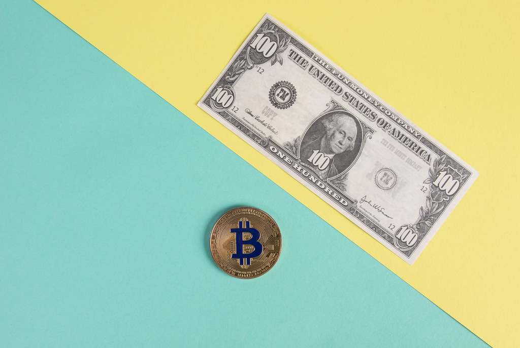Golden Bitcoin coin and  one hundred dollar banknote