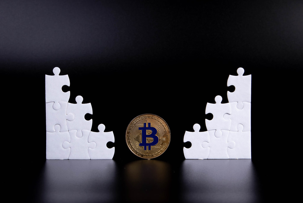 Puzzle pieces with golden Bitcoin coin on black background