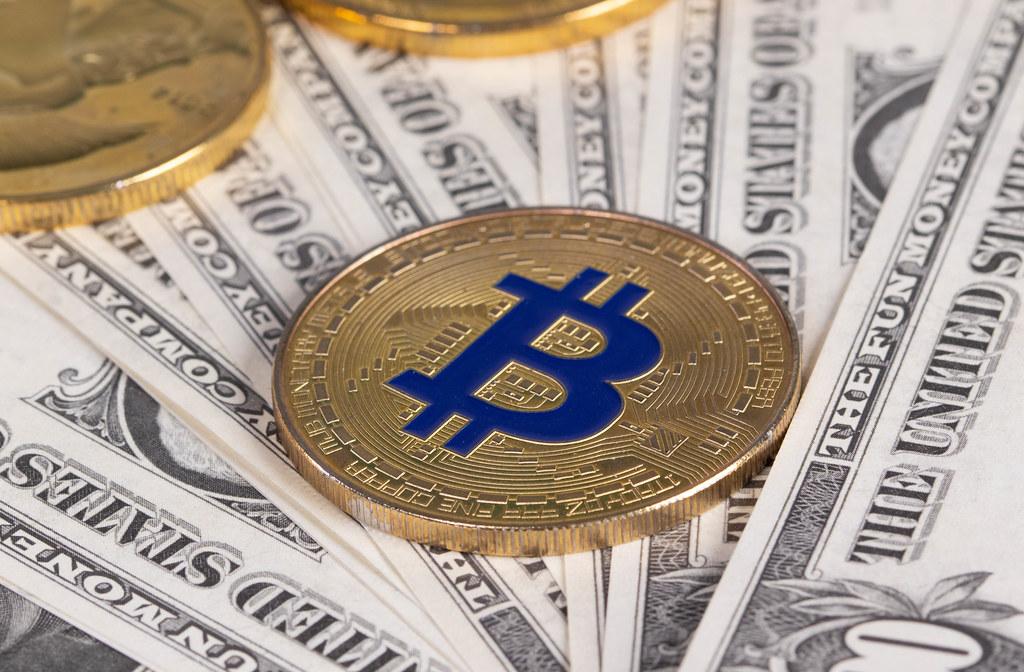 Golden Bitcoin on dollars banknotes