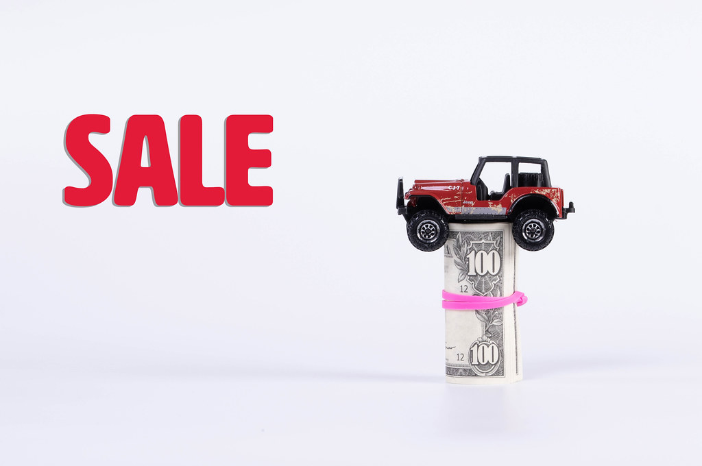 Off-road car with money roll and Sale text on white background
