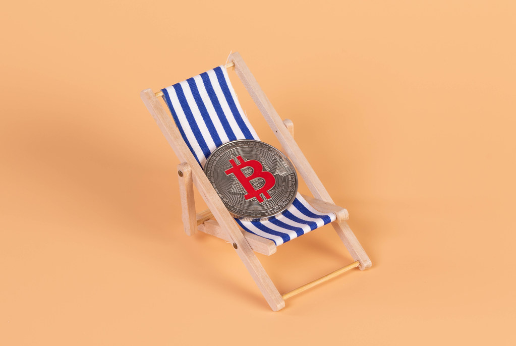 Silver Bitcoin coin lying in a deck chair