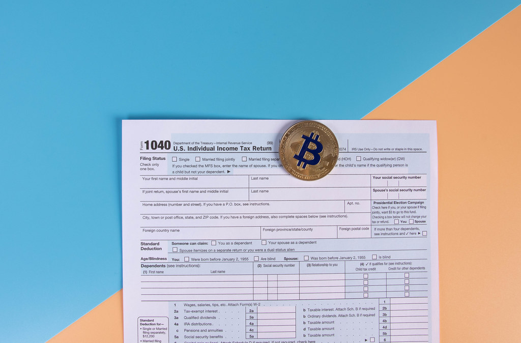 USA tax form 1040 for US individual tax return with golden Bitcoin coin
