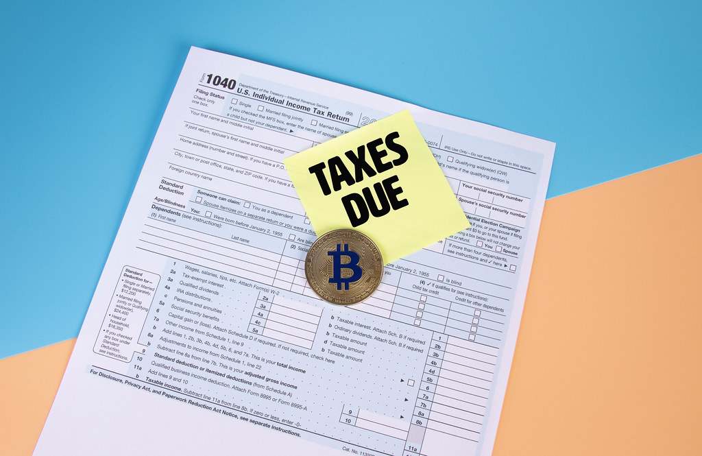 USA tax form 1040 for US individual tax return with golden Bitcoin and sticky note with Taxes Due text