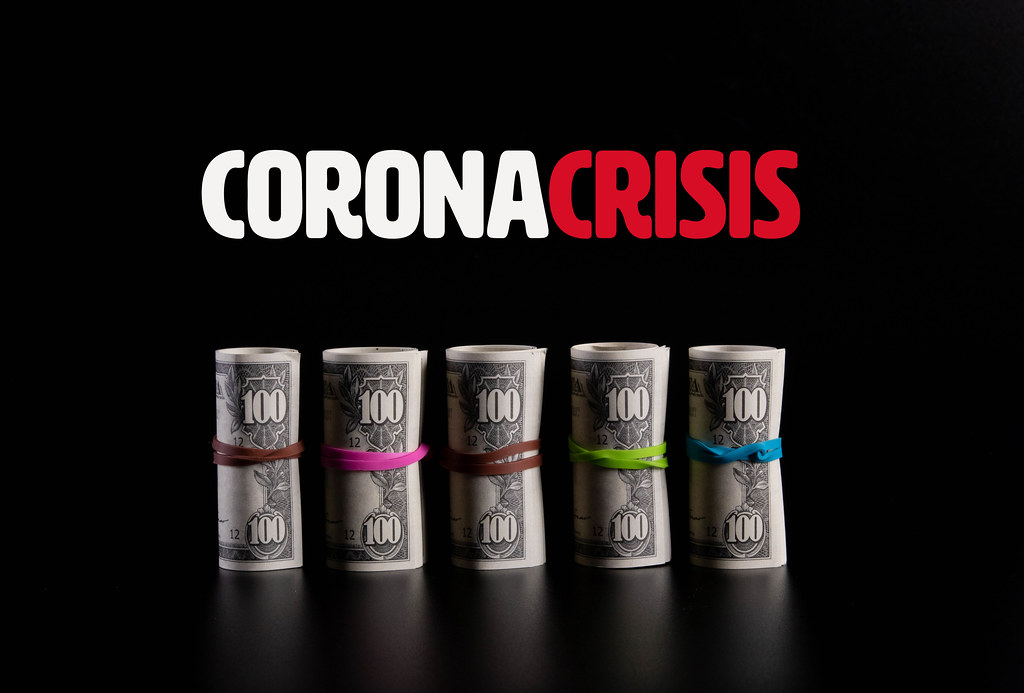Rolls of dollar banknotes with Coronacrisis text on black background