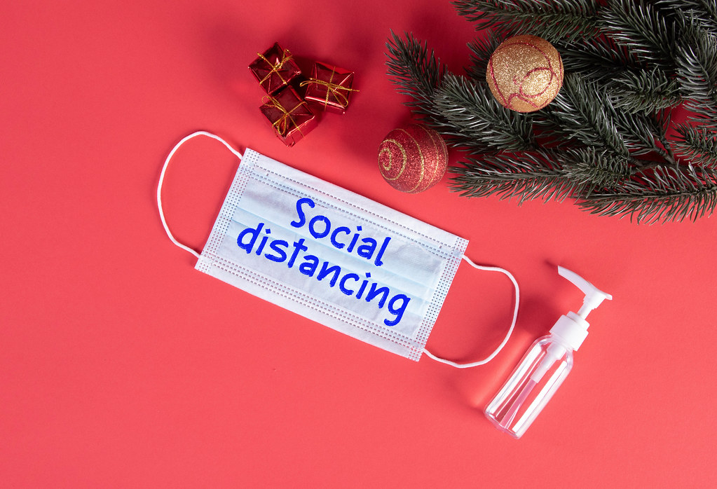 Protective face mask with Social Distancing text and Christmas decorations on red blue background