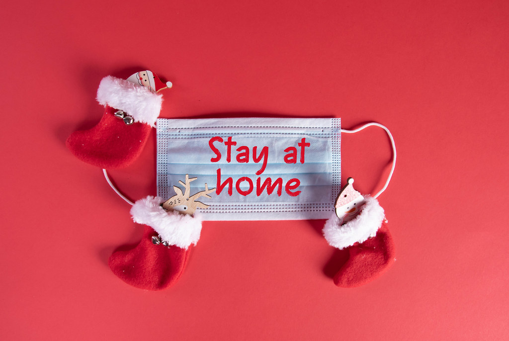 Medical face mask with Stay at home text and christmas socks on red background