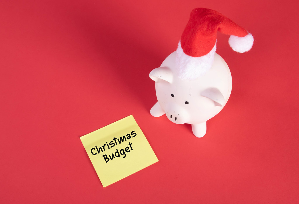 Piggy bank with Christmas hat and sticky note with Christmas Budget text