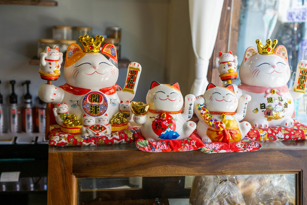 Different sized Maneki-neko Lucky Cats with Golden and Red Decorations to bring Luck in a Cafe in Ho Chi Minh City, Vietnam