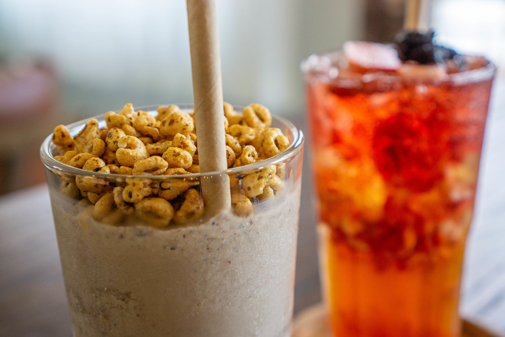 Close Up Photo of Puffed Rice Cereals as a Topping on a Cookies and Cream Milkshake with Paper Straw with Strawberry Ice Tea in the Background