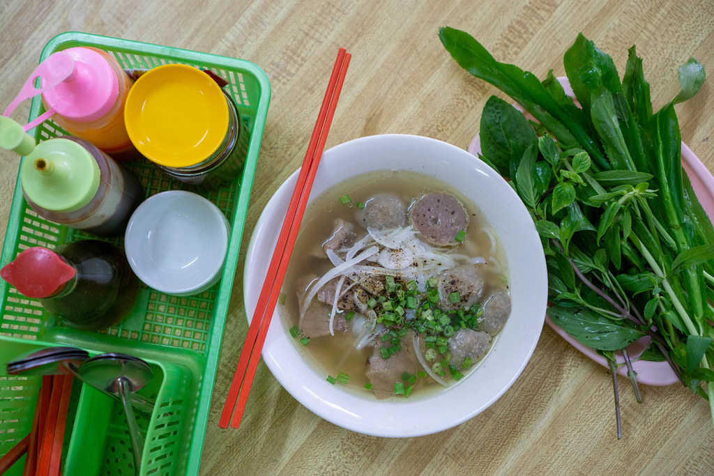 Top View Food Photo of Bowl of Vietnamse National Dish Pho Bo with Beef Balls, Fresh Herbs and Sauces on a Wooden Table
