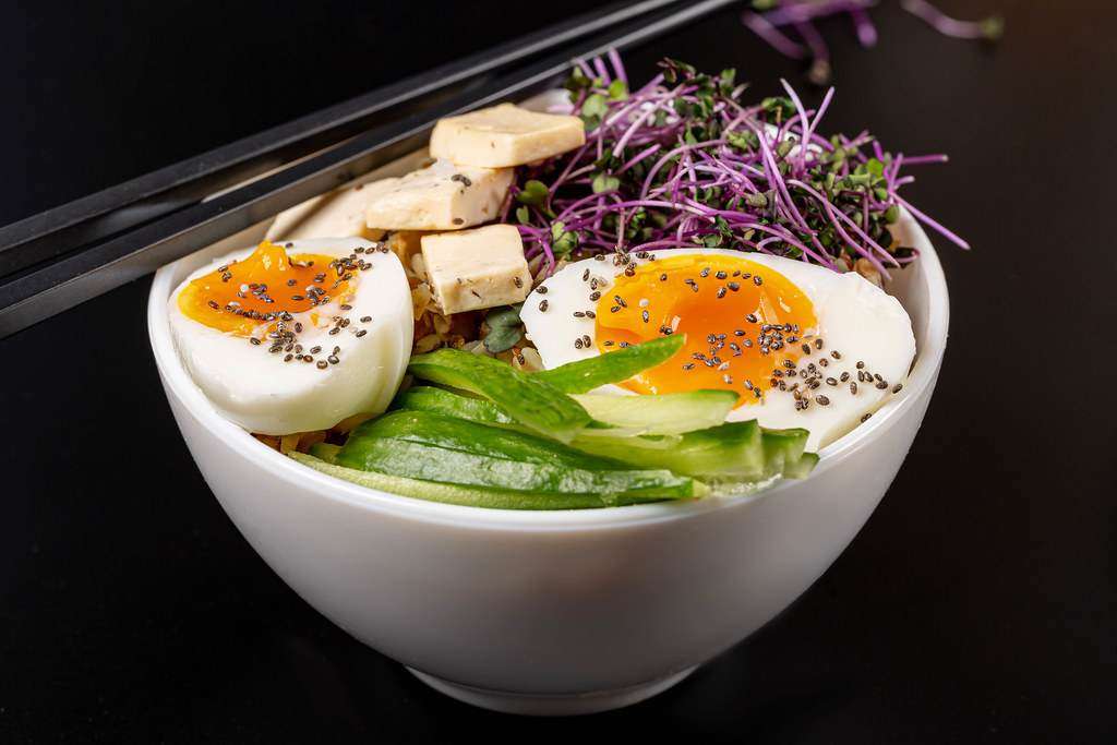 Close-up, bowl of porridge with cucumber, cheese, microgreens and chicken egg