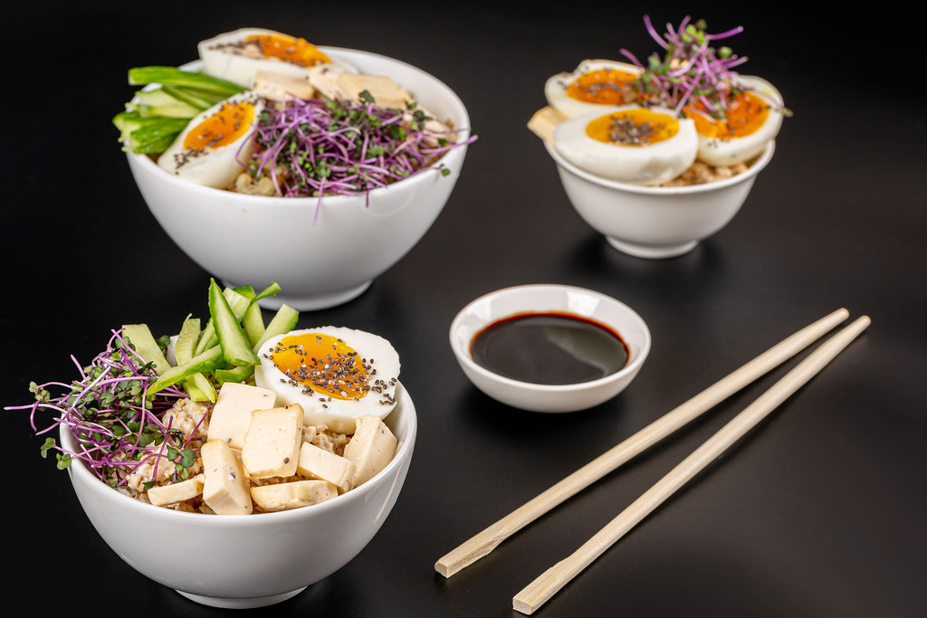 White bowls with oatmeal, cabbage microgreens, cucumber, cheese and boiled eggs on a dark background