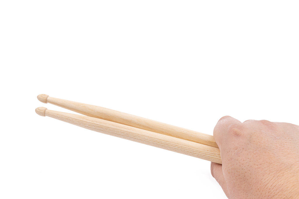 Wooden Drumsticks in the hand above white background with copy space