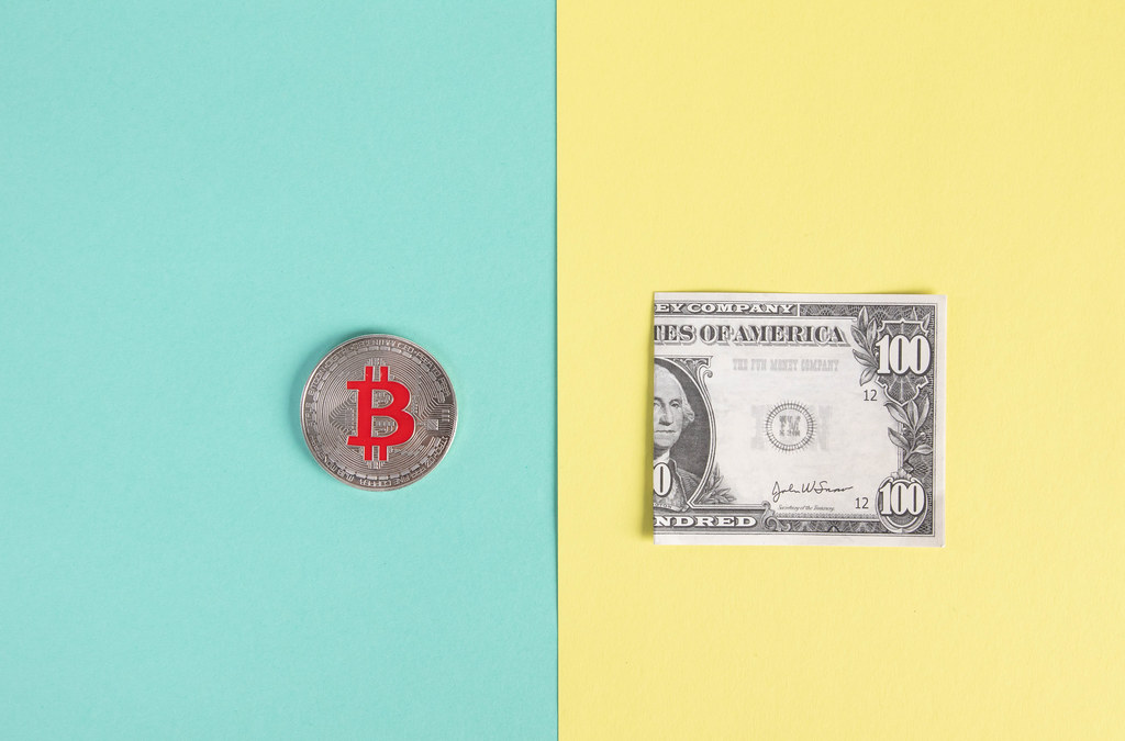 SIlver Bitcoin coin and folded dollar banknote