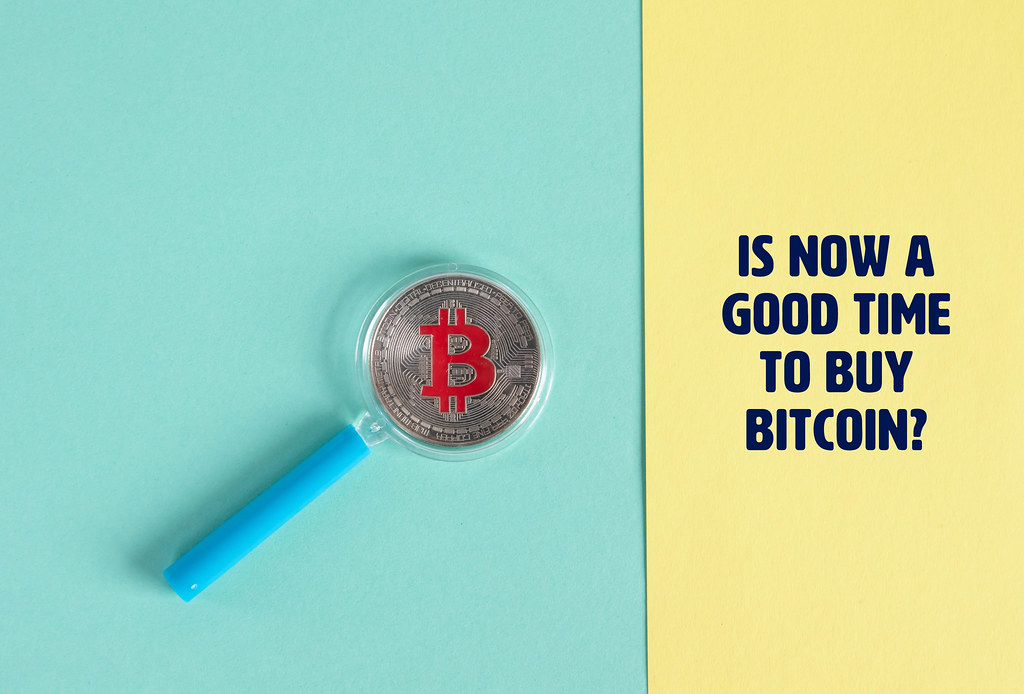 Magnifying glass over sIlver Bitcoin coin and text Is now a good time to buy Bitcoin?